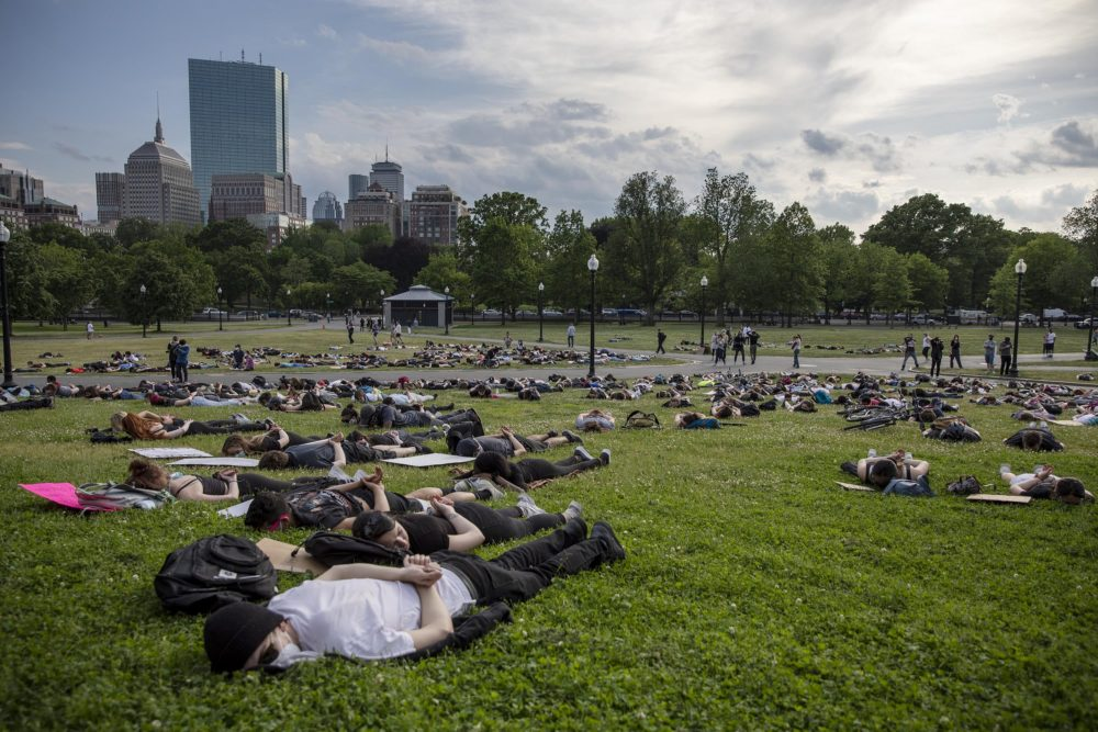 Protesters lie on Boston Common as if handcuffed during a protest on Wednesday. (Robin Lubbock/WBUR)