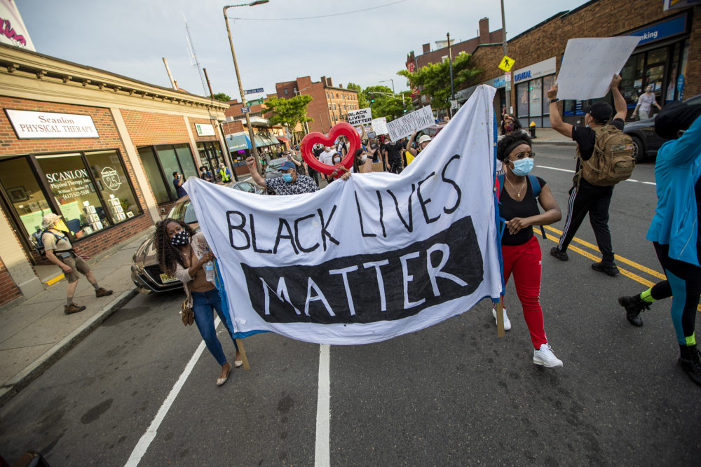 Protesters begin their march down Centre Street towards the Boston Police E-13 District station in Jamaica Plain. (Jesse Costa/WBUR)