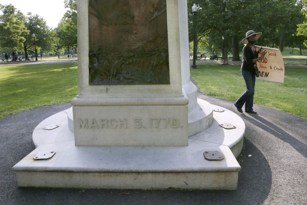 A woman walks past the Boston Massacre Monument on Boston Common on June 3, after a protest against police brutality following the death of George Floyd. The relief sculpture on the monument depicts Crispus Attucks, a black man and first person gunned down by British troops during the Boston Massacre on March 5, 1770. The attack helped touch off the American Revolution. (Charles Krupa/AP)