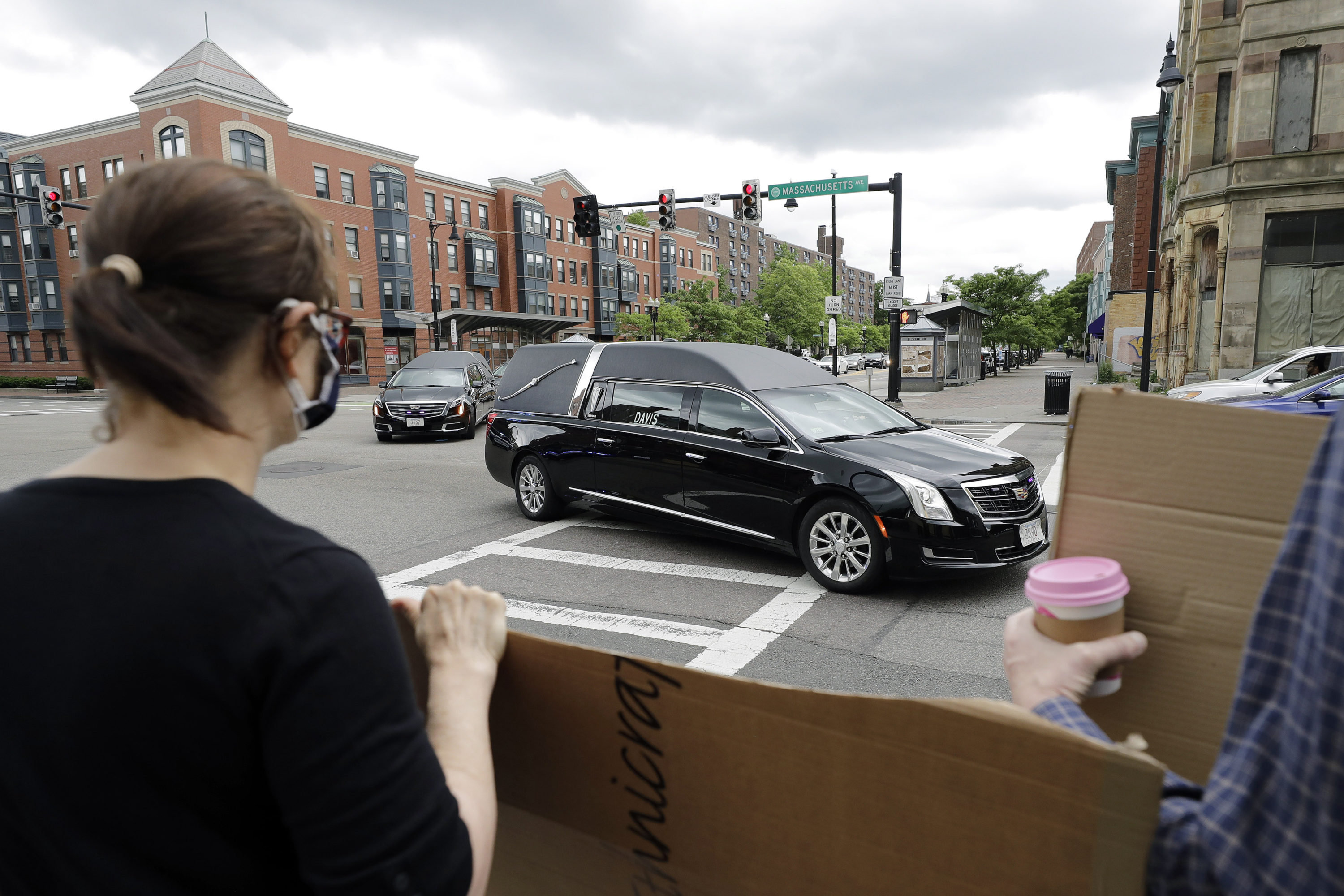 People display placards Sunday while watching a procession of vehicles, including three hearses meant to honor fallen George Floyd, Breonna Taylor and Ahmaud Arbery, as it makes its way through Boston. (Steven Senne/AP)