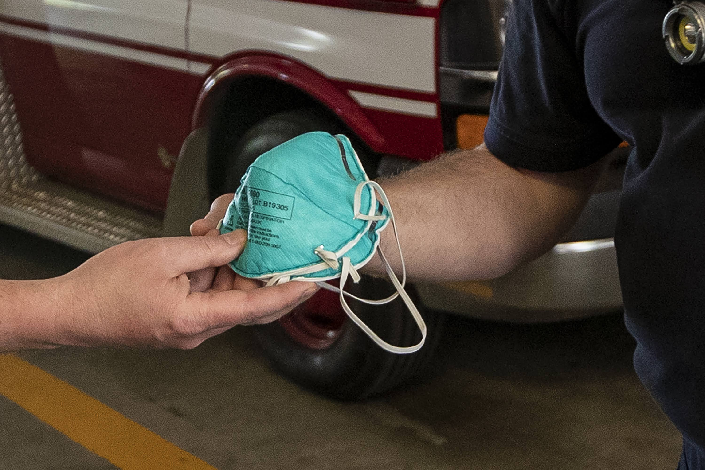 Duxbury Fire Chief Joe Reardon hands N95 masks to paramedic Justin Stratton after he returns from a call. (Jesse Costa/WBUR)