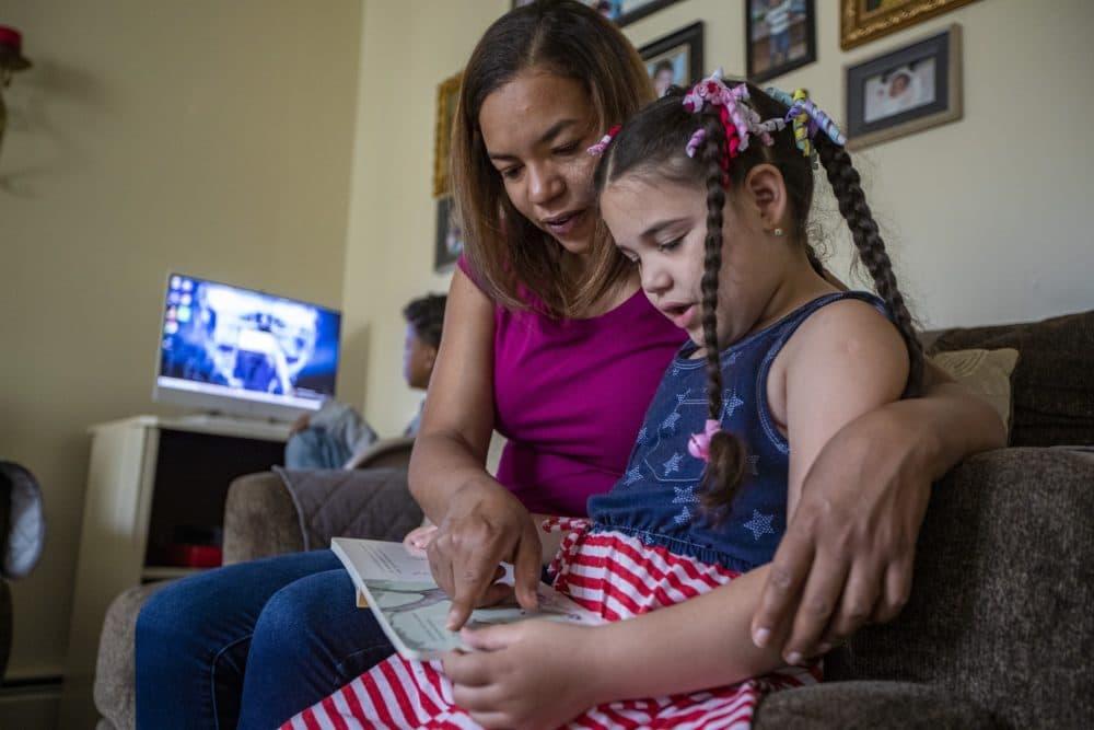 Margareth Jesus y su hija Lucero leen juntas mientras Jesus espera a que comience su clase online. (Jesse Costa/WBUR)