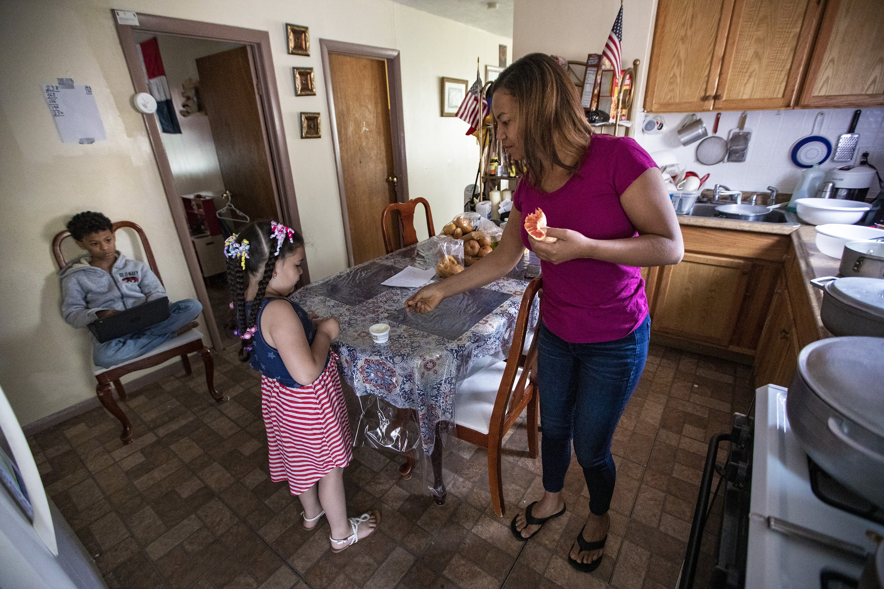 Margareth gives a spoon to Luz to eat her late morning yogurt snack, while Jesus sits on a chair using a laptop. (Jesse Costa/WBUR)