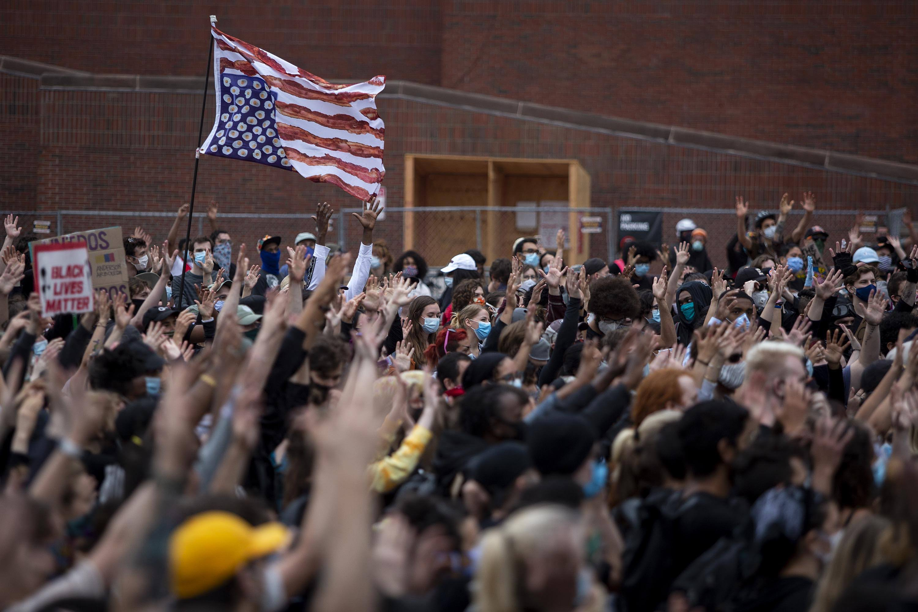 Protesters at the For The People march raise their hands in unison in City Hall Plaza. (Robin Lubbock/WBUR)