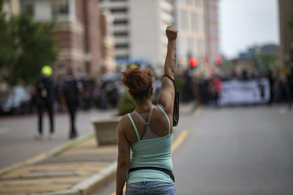A woman raises her fist in the middle of the street by Tufts Medical Center as hundrreds of protesters  march up Washington Street en route to Boston City Hall during the F.T.P. March to Defund Police and Fund Our Communities. (Jesse Costa/WBUR)