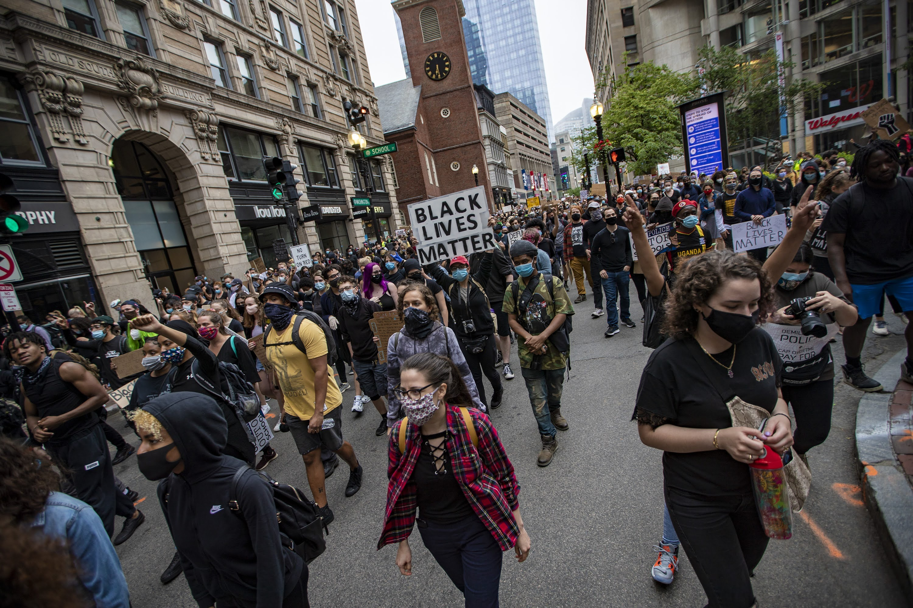 Hundrreds of protesters  march up Washington Street past the Old South Meeting House en route to Boston City Hall during the F.T.P. March to Defund Police and Fund Our Communities. (Jesse Costa/WBUR)