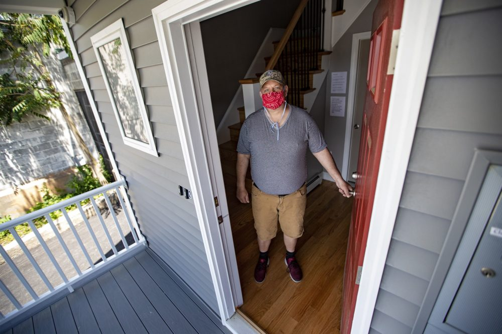 Ed Alger stands in the doorway of the building he moved into recently, which is operated by Father Bill's & MainSpring. The six previously homeless men living in the Brockton property will get on-site support services. (Jesse Costa/WBUR)
