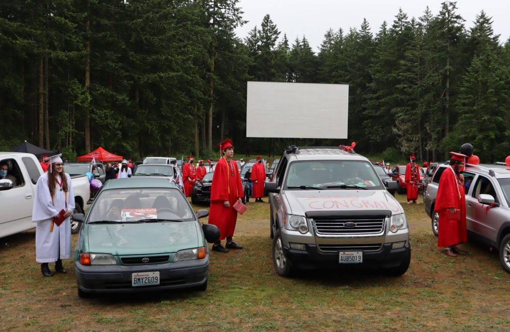 Port Townsend High School seniors stepped outside their vehicles to receive their diplomas during the 2020 graduation ceremony held at the local drive-in movie theater. (Tom Banse/Northwest News Network)