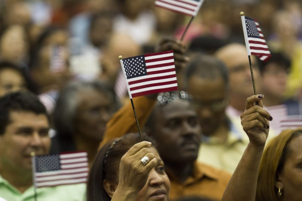 "Brand-new U.S. citizens wave flags during a rendition of ""America the Beautiful"" at the Hynes Convention Center in 2016. (Joe Difazio for WBUR)"