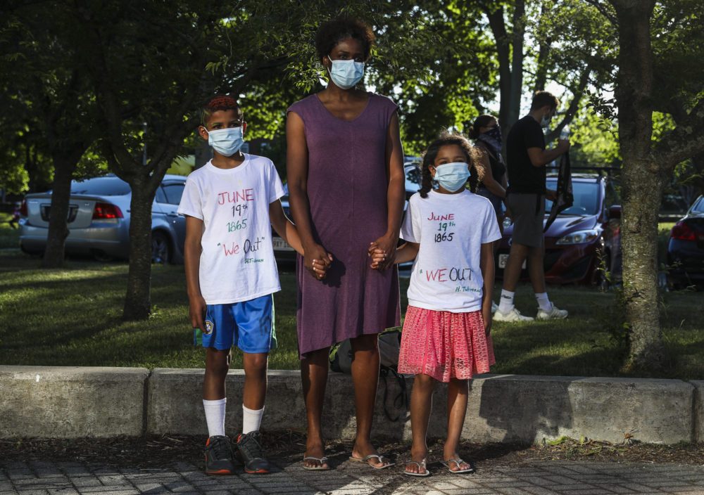 Teronda Ellis stands with her children Finn, 9, left, and Soling, 7, before they march in a Juneteenth Awareness Walk that began at the Boys & Girls Club and walked to Franklin Park in Dorchester. (Erin Clark/The Boston Globe via Getty Images)