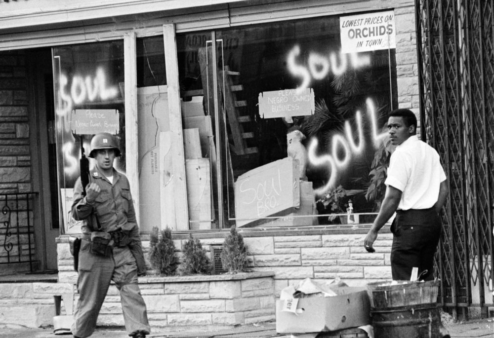In this July 15, 1967 file photo a National Guard officer passes the smashed window of a Black-owned flower shop in riot-torn Newark, N.J. The last surviving member of the Kerner Commission says he remains haunted that the panel's recommendations on U.S. race relation and poverty were never adopted, but he is hopeful they will be one day. (AP Photo,File)