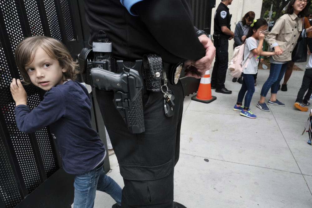 Julian Richner, 9, leaves school for the day to meet his mother as he passes behind an armed security guard at Beverly Hills Unified School District's K-8 Horace Mann School in Beverly Hills, Calif. on Monday, May 13, 2019. Districts nationwide are employing a multi-layered approach for safety that combines mental health programs, bullying prevention initiatives with hardware and software technology, as well as armed and unarmed security officers. (Richard Vogel/AP)