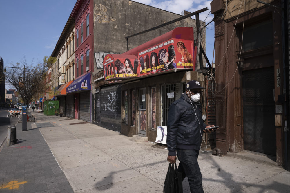 A man wearing a mask walks past Sogho Express African Hair Braiding salon, which is closed due to the coronavirus pandemic, Tuesday, April 7, 2020 in the Bedford Stuyvesant neighborhood of New York. (Mark Lennihan/AP)