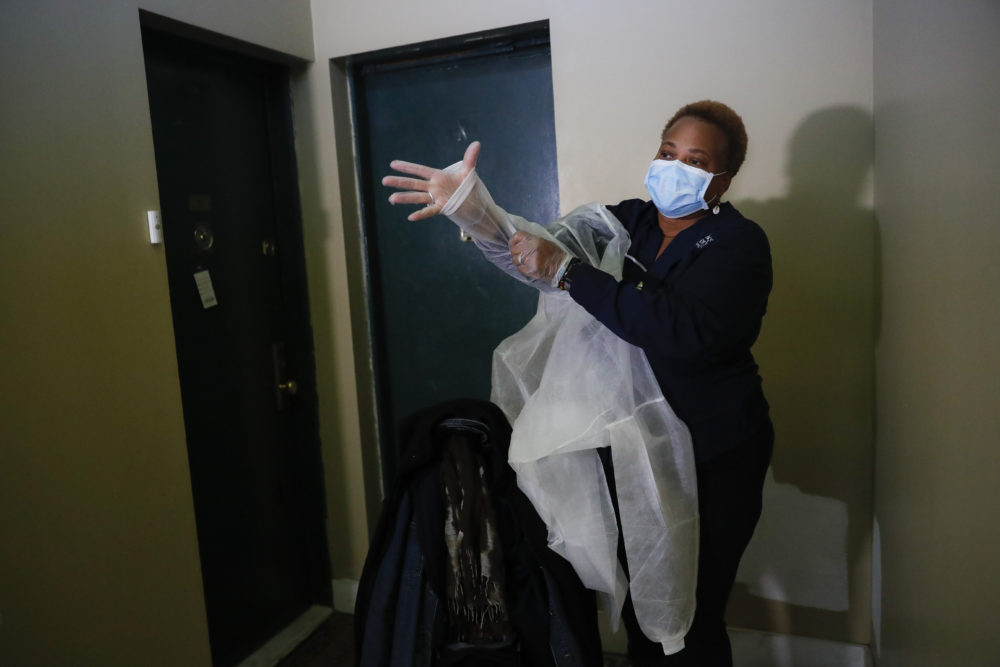 In this Thursday, April 23, 2020 photo, Ruth Caballero, a nurse with The Visiting Nurse Service of New York, puts on personal protective equipment before entering a patient's apartment as she makes her rounds in upper Manhattan in New York. (John Minchillo/AP Photo)