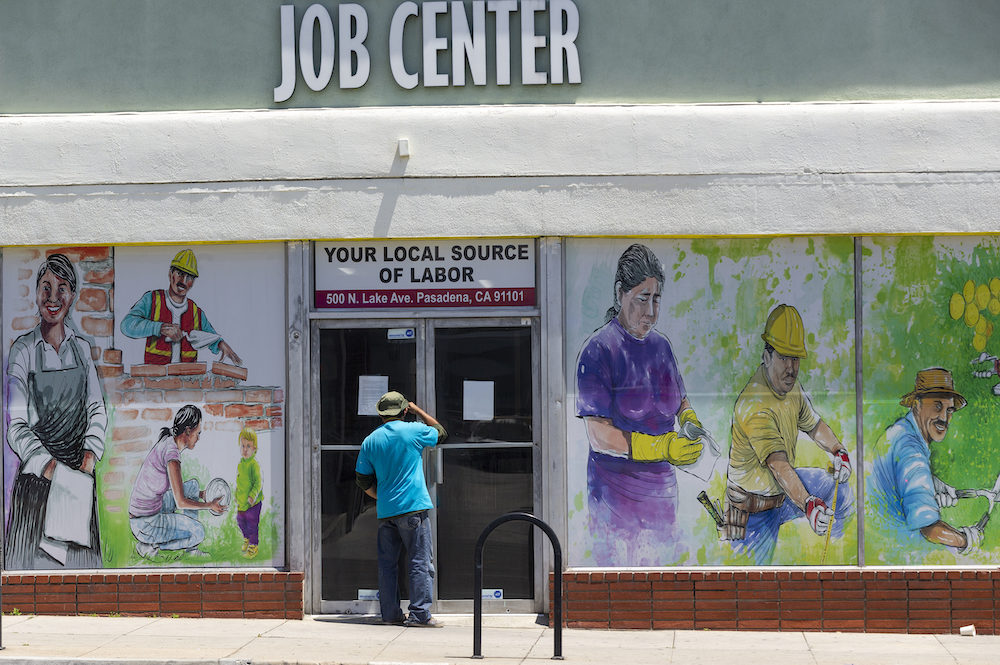 A worker looks inside the closed doors of the Pasadena Community Job Center in Pasadena, Calif.,  Thursday, May 7, 2020, during the coronavirus outbreak. (Damian Dovarganes/AP Photo)