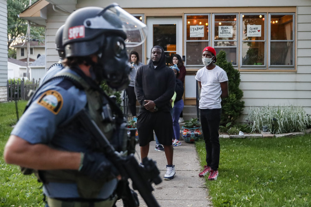 Protestors watch as police in riot gear walk down a residential street, Thursday, May 28, 2020, in St. Paul, Minn. (John Minchillo/AP Photo)