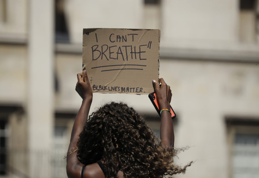 A woman holds up a banner as people gather in Trafalgar Square in central London on Sunday, May 31, 2020 to protest against the recent killing of George Floyd by police officers in Minneapolis that has led to protests across the US. (Matt Dunham/AP)