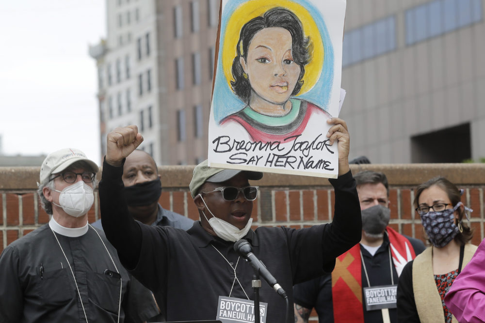 Kevin Peterson, founder and executive director of The New Democracy Coalition, center, displays a placard showing fallen Breonna Taylor as he addresses a rally n Boston. Petersen advocates for changing the name of Faneuil Hall, as its namesake Peter Faneuil, was a slave owner. (Steven Senne/AP)