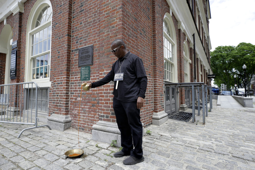 During a June protest outside of Faneuil Hall, Kevin Peterson pours a red substance meant to symbolize the blood of fallen black people who died under under white suppression and slavery. (Steven Senne/AP)
