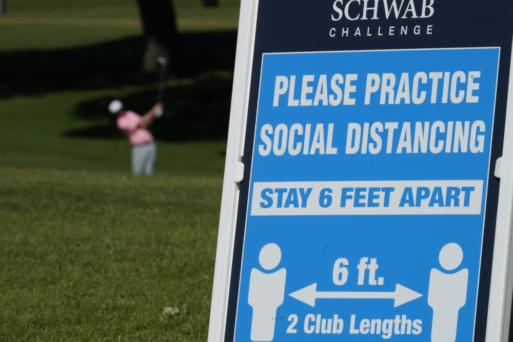 Signs remind golfers of social distancing rules during the first round of the Charles Schwab Challenge golf tournament at the Colonial Country Club in Fort Worth, Texas, Thursday, June 11, 2020. (David J. Phillip/AP)