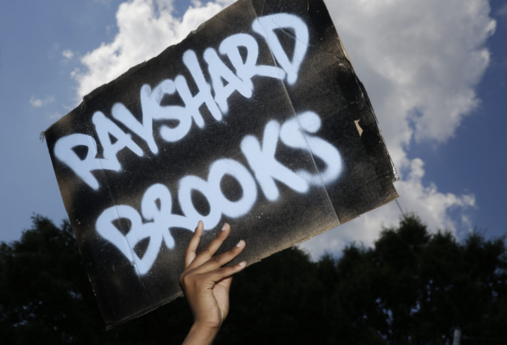 A protester holds up a sign on Saturday, June 13, 2020, near the Wendy's restaurant where Rayshard Brooks was shot and killed by police Friday evening following a struggle in the restaurant's drive-thru line in Atlanta. (Brynn Anderson/AP)