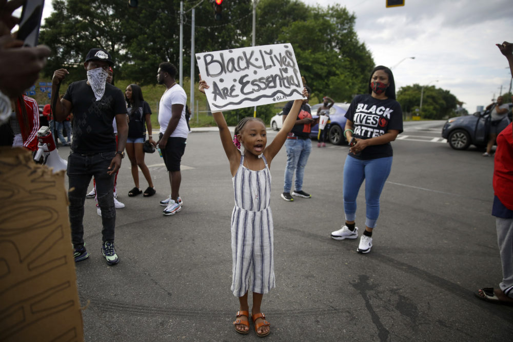 "A young protester yells ""Black Lives Matter"" in the street near a Wendy's restaurant on Wednesday, June 17, 2020 in Atlanta. The restaurant was where Rayshard Brooks was shot and killed by police. (AP Photo/Brynn Anderson)"