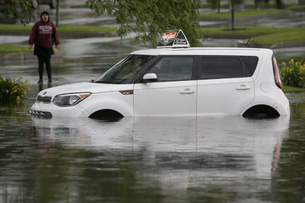 A woman speaks to a person in a vehicle stranded in water on Sunday on a flooded street in Norwood, Mass. (Steven Senne/AP)