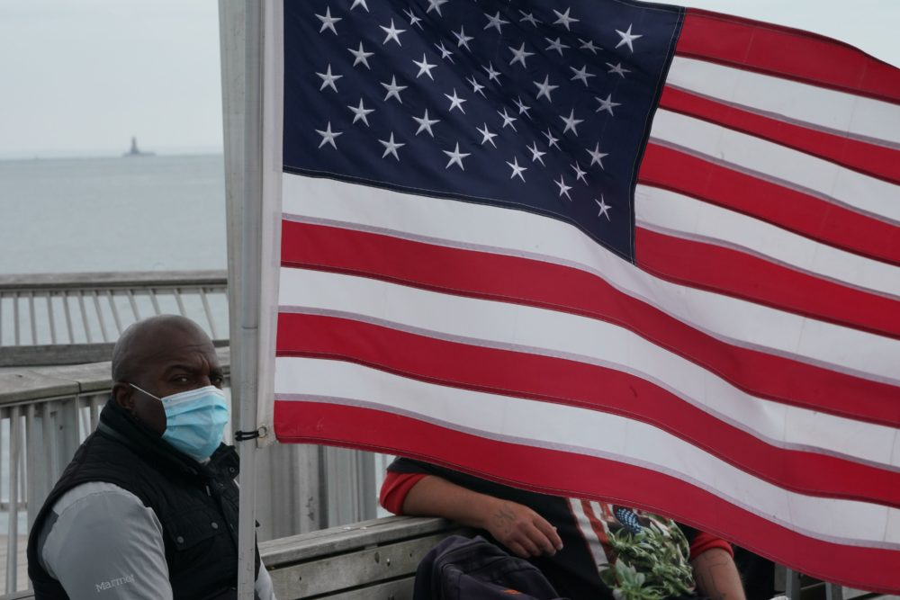 A man wearing a face mask sits near an American flag on a pier at Coney Island amid the coronavirus pandemic on May 24, 2020 in New York. (Bryan R. Smith/AFP/Getty Images)