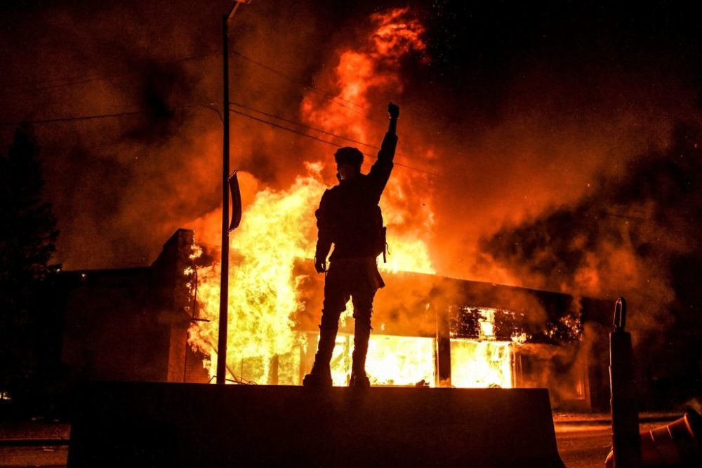 A protester reacts standing in front of a building set on fire during a demonstration in Minneapolis on May 29, 2020, over the death of George Floyd at the hands of police. (Chandan Khanna/AFP/Getty Images)