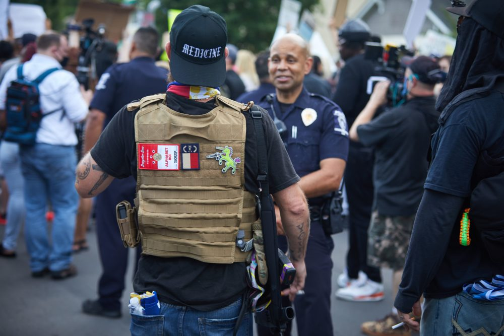 A member of the far-right militia, Boogaloo Bois, walks next to protesters demonstrating outside Charlotte Mecklenburg Police Department Metro Division 2 just outside of downtown Charlotte, North Carolina, on May 29, 2020. (Logan Cyrus/AFP/Getty Images)