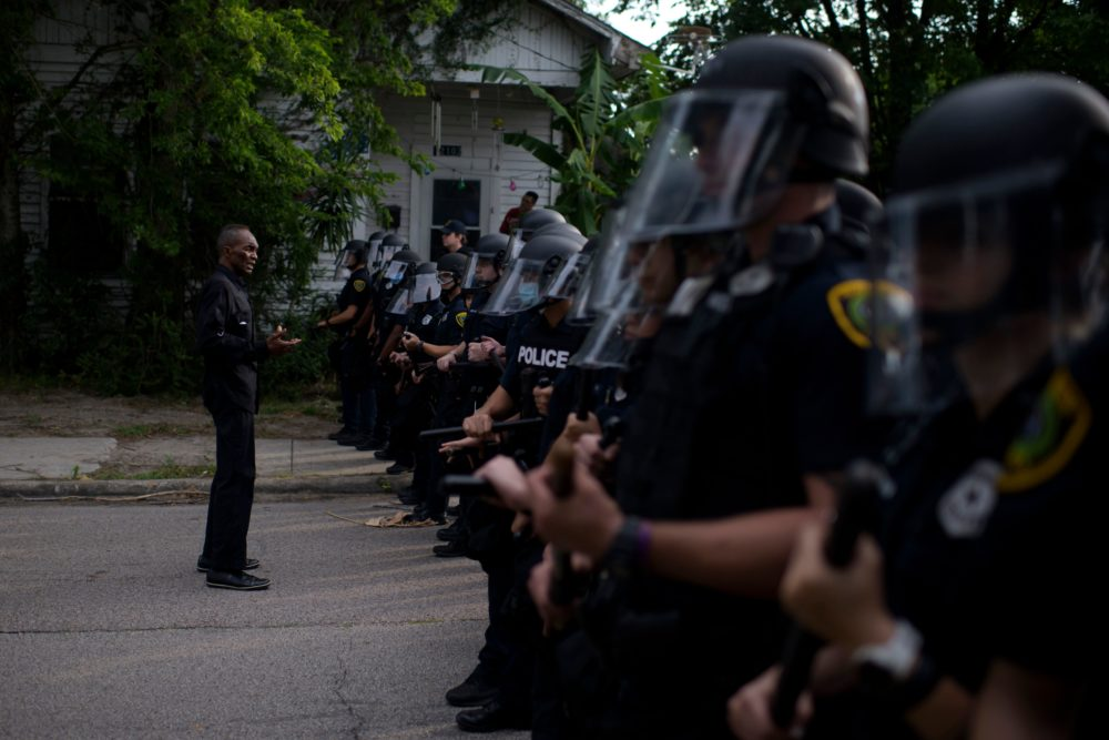 "A man addresses a row of police officers during a ""Justice for George Floyd"" event in Houston, Texas on May 30, 2020, after George Floyd, an unarmed black, died while being arrested and pinned to the ground by a Minneapolis police officer. (MARK FELIX/AFP via Getty Images)"