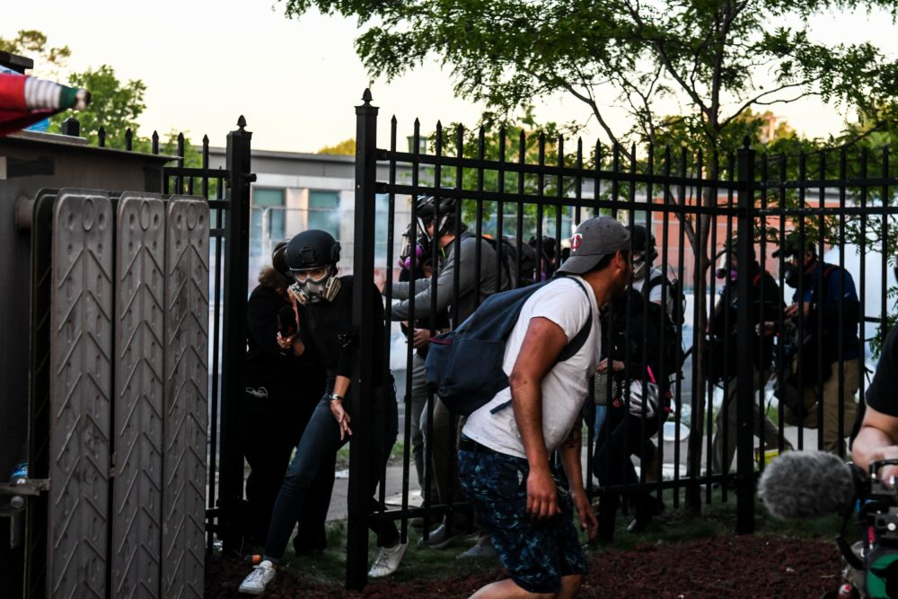 Protestors and media personnel run to take cover as police start firing tear gas and rubber bullets near the 5th police precinct following a demonstration to call for justice for George Floyd, a black man who died while in custody of the Minneapolis police, on May 30, 2020 in Minneapolis, Minnesota. (Photo by CHANDAN KHANNA/AFP via Getty Images)