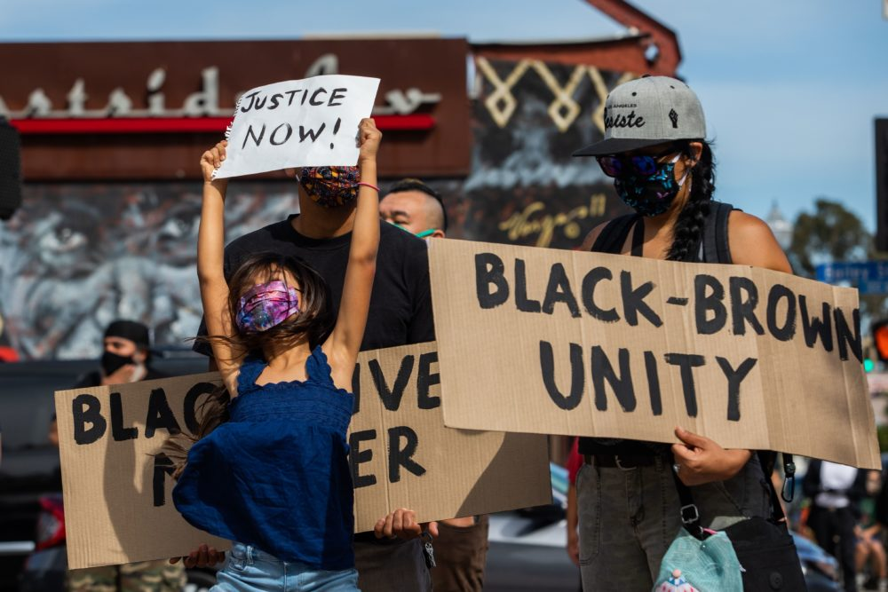 A girl jumps holding a sign (Justice Now!) while she and her family protest in the Boyle Heights neighborhood of Los Angeles on May 30, 2020 in response against the death of George Floyd, an unarmed black man who died while while being arrested and pinned to the ground by the knee of a Minneapolis police officer. (APU GOMES/AFP via Getty Images)