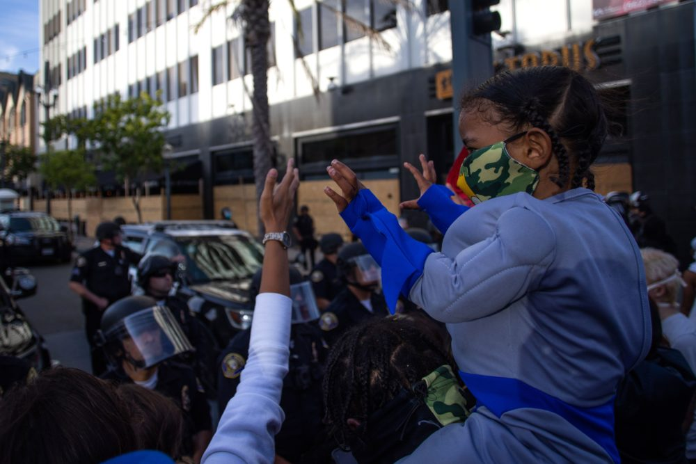 A child holds up his hands in front of a row of police officers in downtown Long Beach on May 31, 2020 during a protest against the death of George Floyd, an unarmed black man who died while being arrested and pinned to the ground by the knee of a Minneapolis police officer. (APU GOMES/AFP via Getty Images)