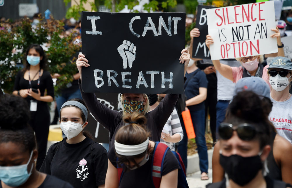 Peaceful demonstrators hold signs as they protest the death of George Floyd outside the Bethesda Library on June 2, 2020 in  Bethesda, Maryland. (Olivier Douliery/AFP via Getty Images)