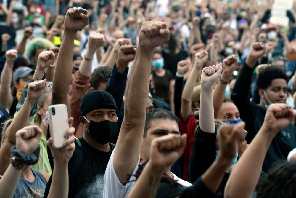 Demonstrators raise their fists in a sign of solidarity while protesting the death of George Floyd, an unarmed black man who died while while being arrested and pinned to the ground by the knee of a Minneapolis police officer, at the  Colorado State Capital in Denver, Colorado on June 3, 2020. (Jason Connolly/AFP)