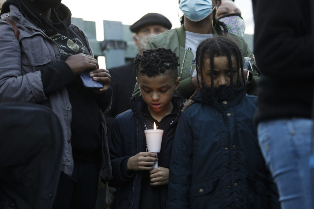 In this June 3, 2020 photo in Tacoma, Washington a boy holds a candle as family, friends and community members attend a vigil at the intersection where Manuel Ellis, a 33-year-old black man, died in Tacoma Police custody on March 3. (Jason Redmond/AFP via Getty Images)