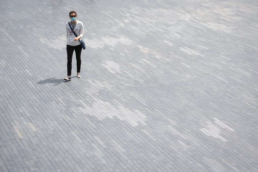 A woman wearing a protective face mask walks alone near Tower Bridge, in London, following the introduction of measures to bring England out of lockdown. (Dominic Lipinski/PA Images via Getty Images)
