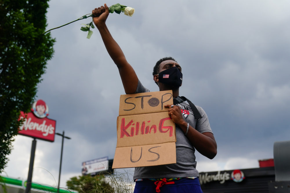 A man holds a sign and a white rose in his fist while facing traffic outside a burned Wendy's restaurant on the second day following the police shooting death of Rayshard Brooks in the restaurant parking lot June 14, 2020, in Atlanta, Georgia. (ELIJAH NOUVELAGE/AFP via Getty Images)