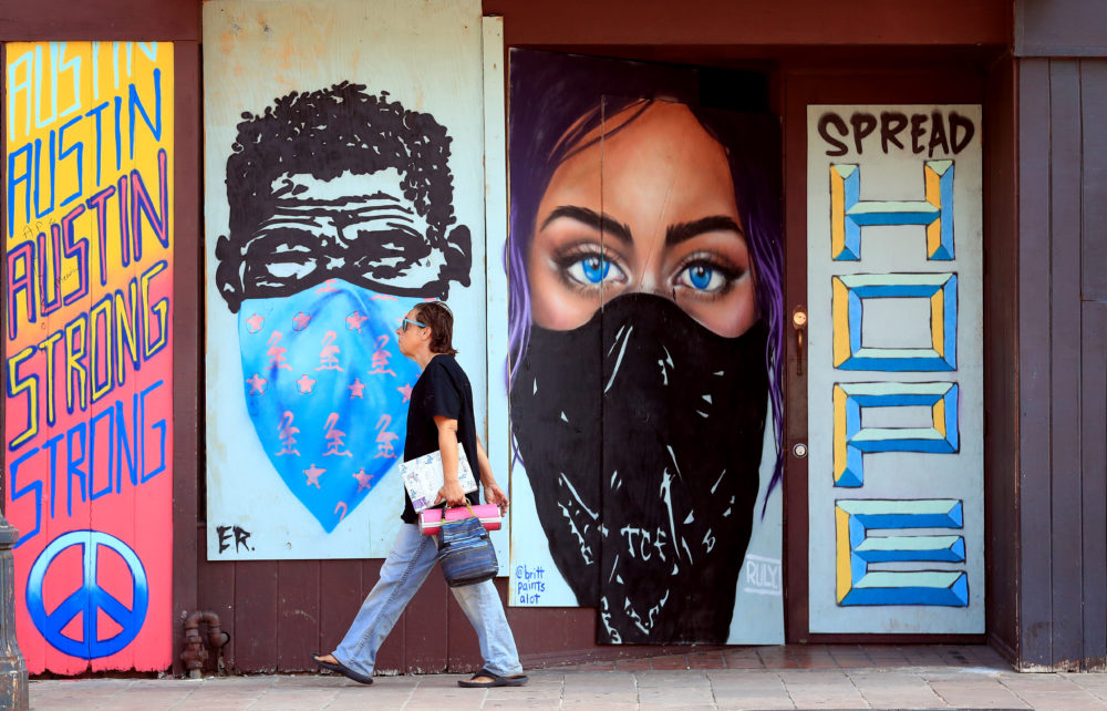Pedestrians walk past murals painted on boards covering bar windows on 6th Street on May 20, 2020 in Austin, Texas. (Tom Pennington/Getty Images)