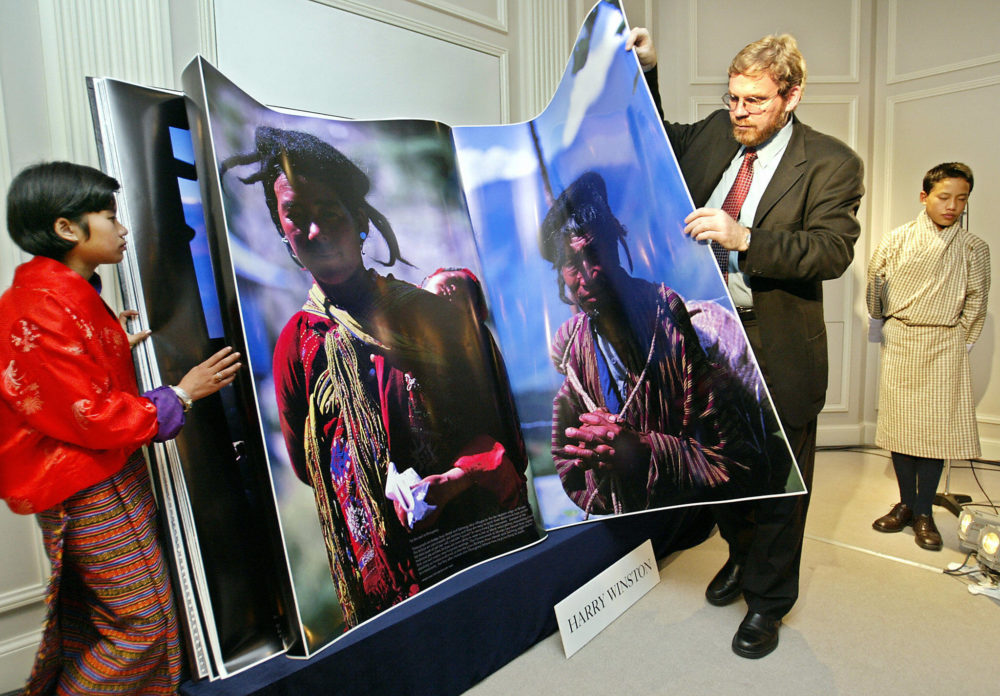 """In this 2003 photo, MIT's Michael Hawley turns a page of his book """"Bhutan, A Visual Odyssey Across the Kingdom"""" to introduce the Himalayan country while Bhutanese boy Gyelsey Loday (R) and girl Choki Lhamo (L) look on during a preview in Tokyo. (TORU YAMANAKA/AFP via Getty Images)"""