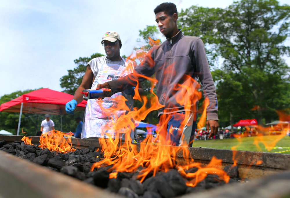 Ralph Johnson, left, and his nephew John Jackson Jr light the charcoal fire on his grill during a Juneteenth celebration at the Franklin Park Playstead in the Dorchester neighborhood of Boston on June 16, 2018. (John Tlumacki/The Boston Globe via Getty Images)