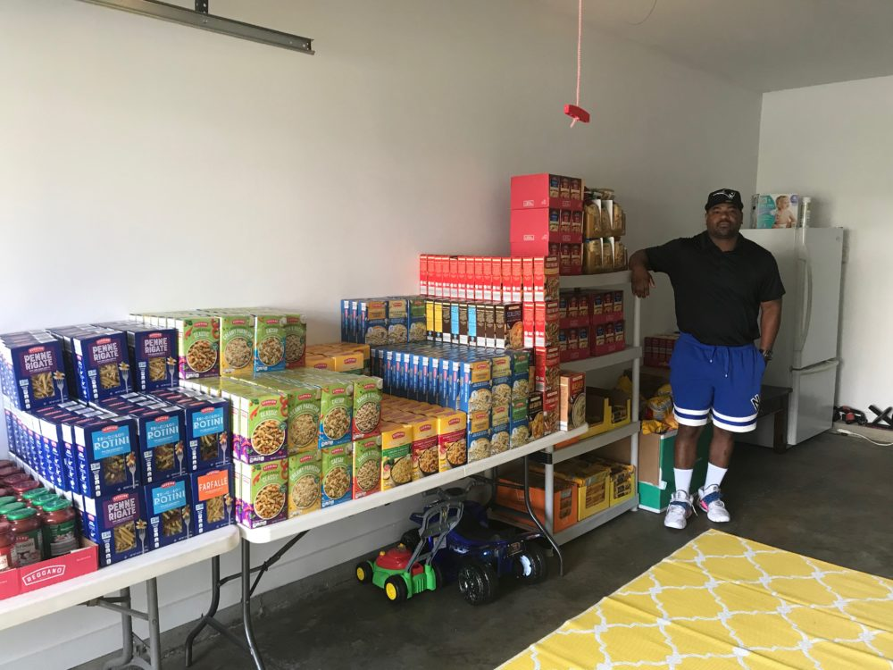 """Maurice Humphrey in his garage in Vernon, Conn., where he keeps his stockpile of groceries that he and his volunteers deliver to families in need, all purchased from donated funds from Maurice's """"$20 Challenge."""" (Courtesy)"""
