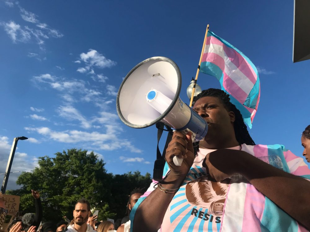 "Athena Vaughn, with the Massachusetts Transgender Political Coalition, speaks through a bullhorn to the crowd at the ""Trans Resistance Rally and March"" Saturday. (Quincy Walters/WBUR)"