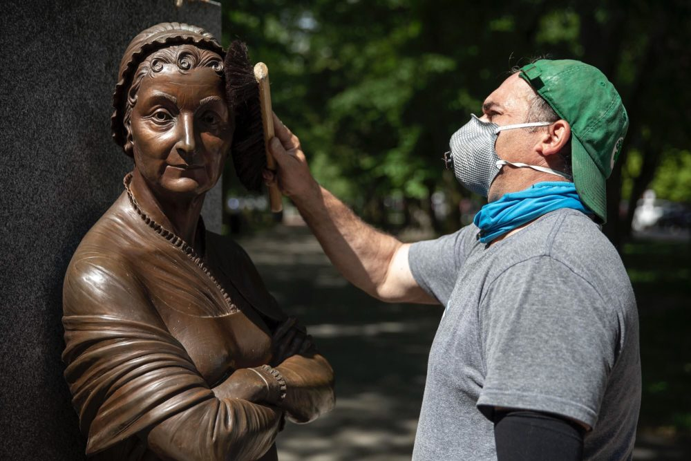 Sculpture conservator Joshua Craine completes the cleanup of the Abigail Adams statue at the Boston Women's Memorial on Commonwealth Avenue Mall. (Robin Lubbock/WBUR)