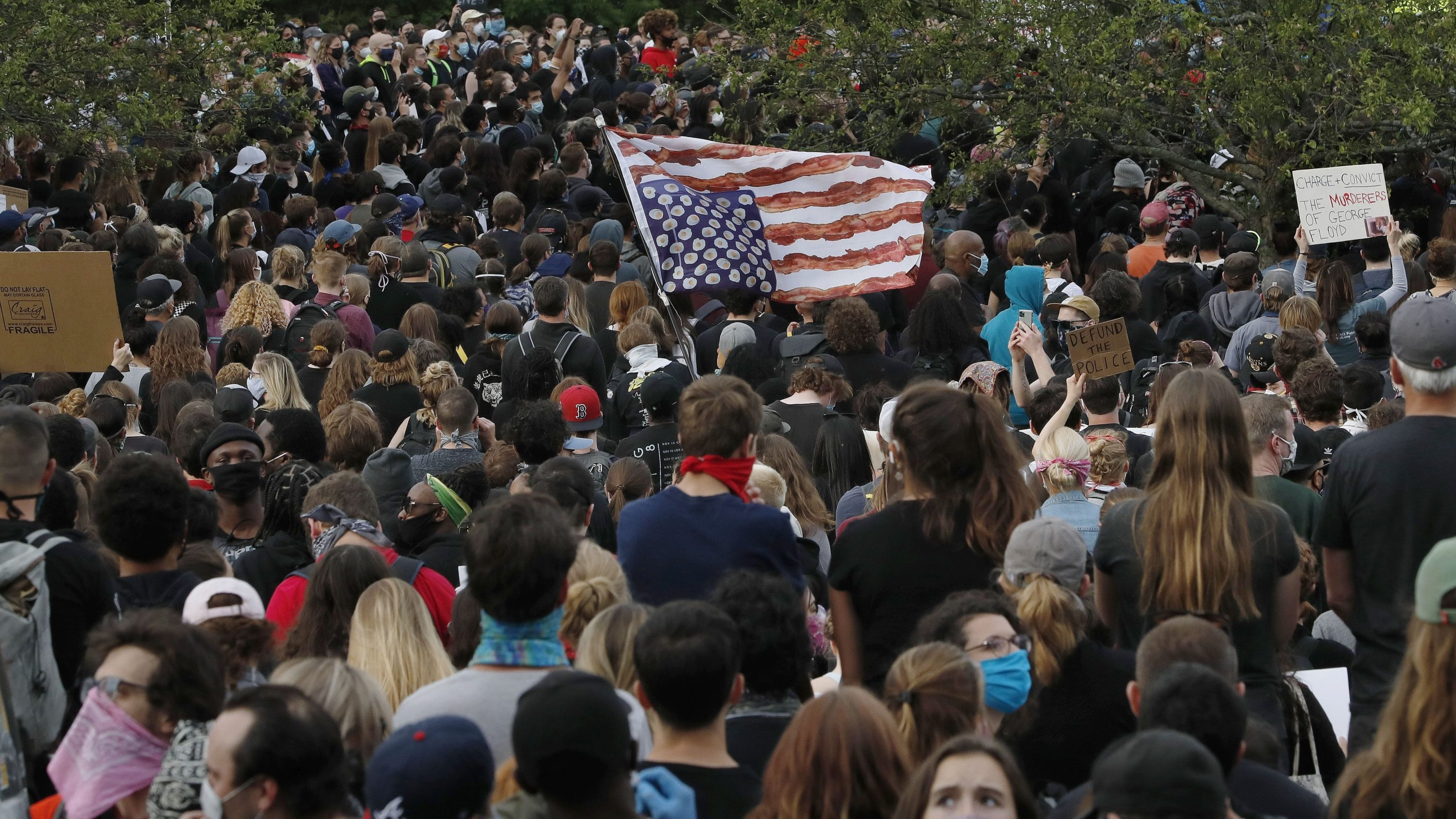 A stylized American flag is held upside down among hundreds gathered in Boston on Tuesday to protest against police brutality following the death of George Floyd. (Charles Krupa/AP)