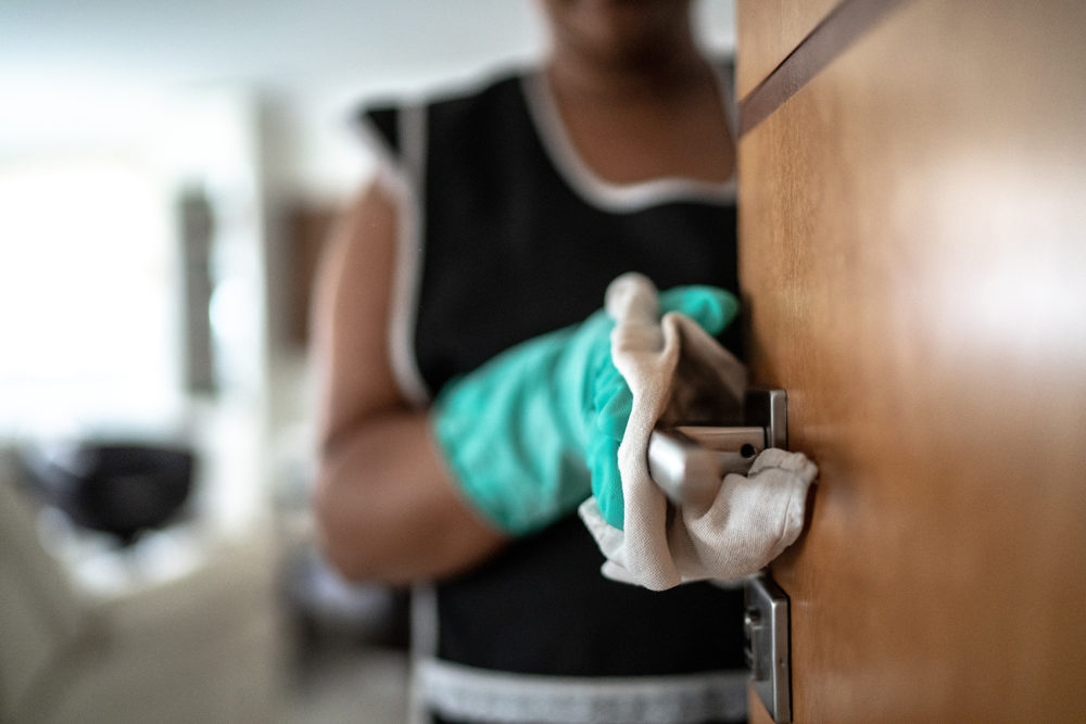 A woman uses a gloved hand to wipe down a doorknob. (FG Trade/Getty Images)