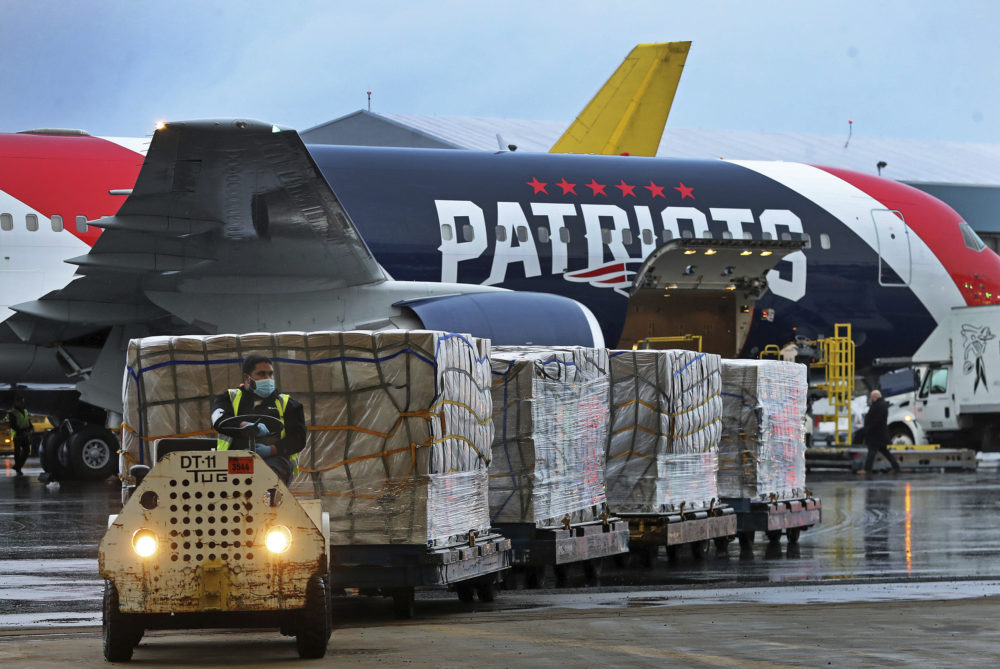 Palettes of N95 respirator masks are off-loaded from the New England Patriots football team's customized Boeing 767 jet on the tarmac on April 2, 2020, at Boston Logan International Airport in Boston, after returning from China. (Jim Davis/The Boston Globe via AP, pool)