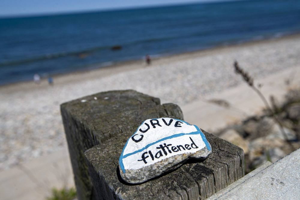 A brightly painted rock with a pandemic-related message was left on top of a guardrail at a virtually empty Brant Rock Beach in Marshfield. (Jesse Costa/WBUR)