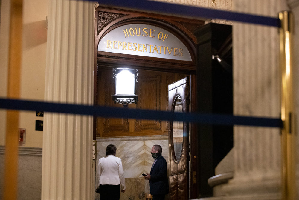 As the third day of House debate on policing reform stretched into the night, House Judiciary Chair Claire Cronin and Rep. Paul Tucker, a retired police chief, conversed in a chamber entryway. (Sam Doran/SHNS)